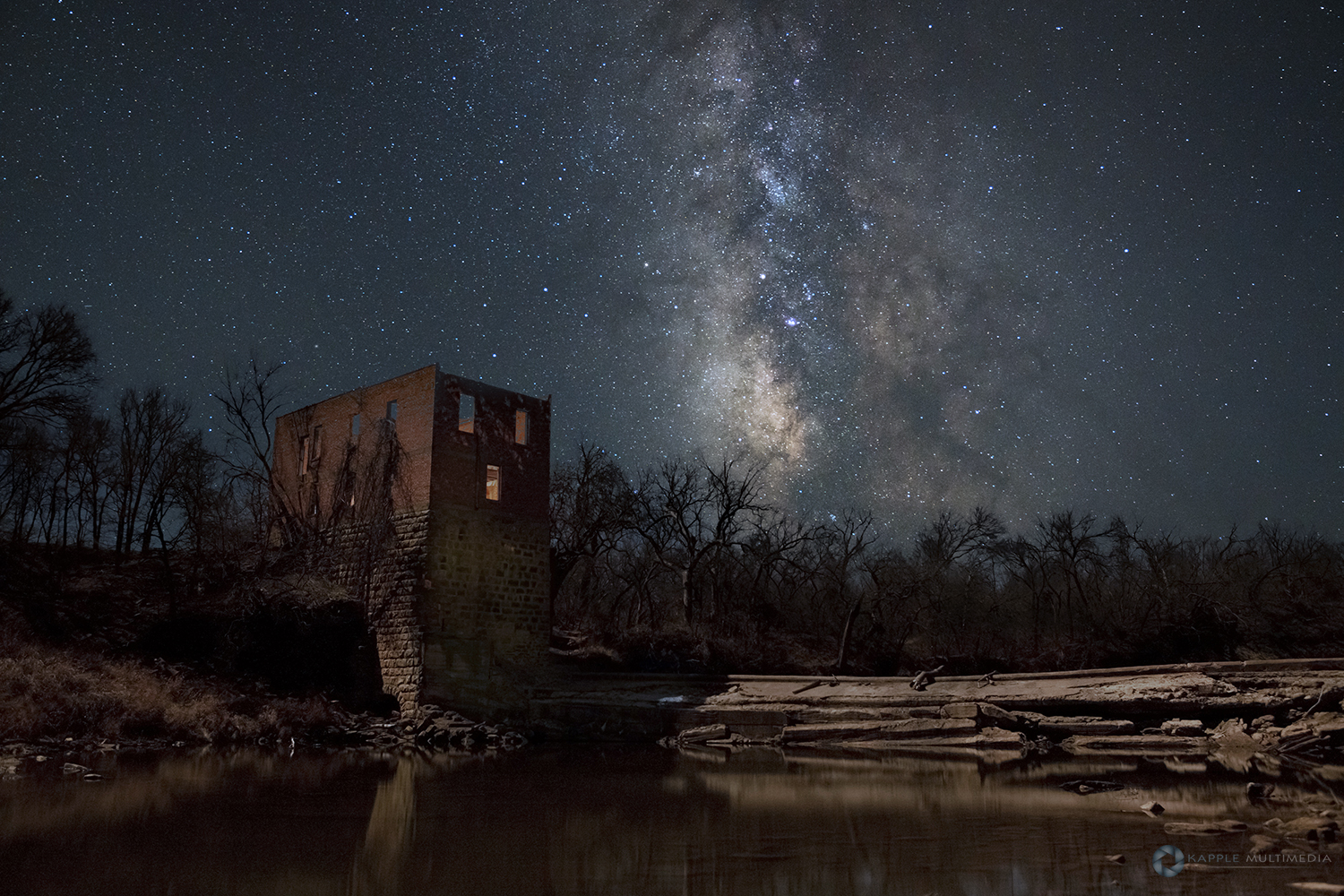 Ruins of an old grist mill lit by moonlight with stars in west Texas